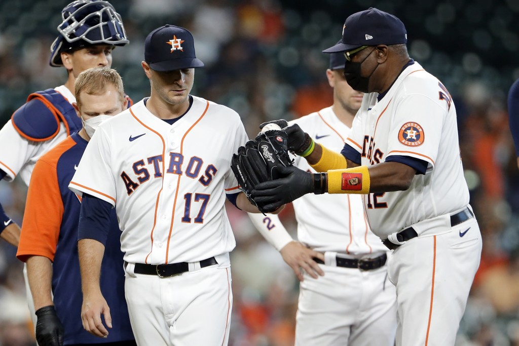 Houston Astros starting pitcher Jake Odorizzi (17) hands the ball off to manager Dusty Baker Jr. (12) as he leaves the mound with an injury on the sec...
