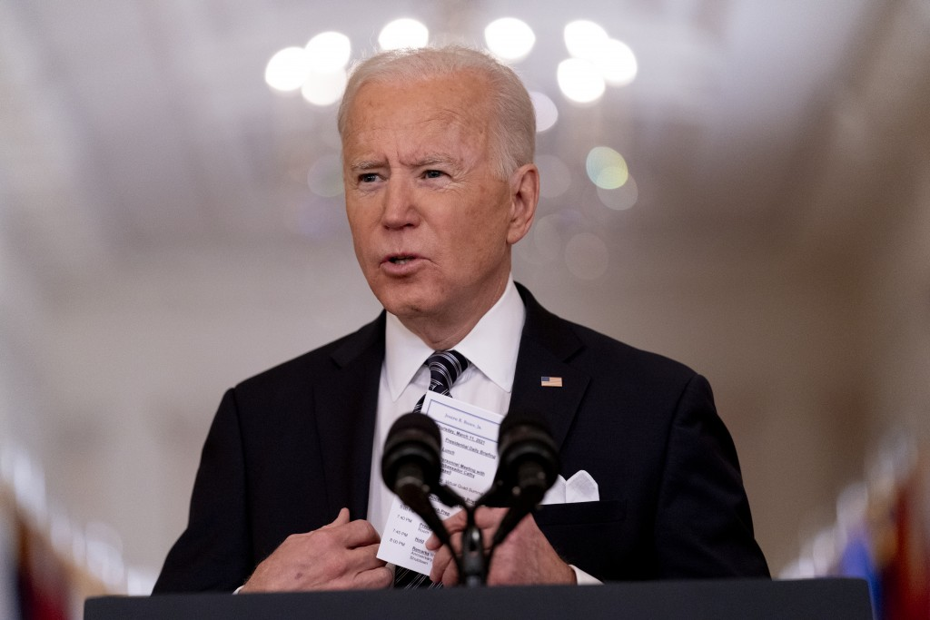 FILE - In this March 11, 2021, file photo President Joe Biden holds up a card with his daily schedule and the daily deaths from COVID-19 as he speaks ...