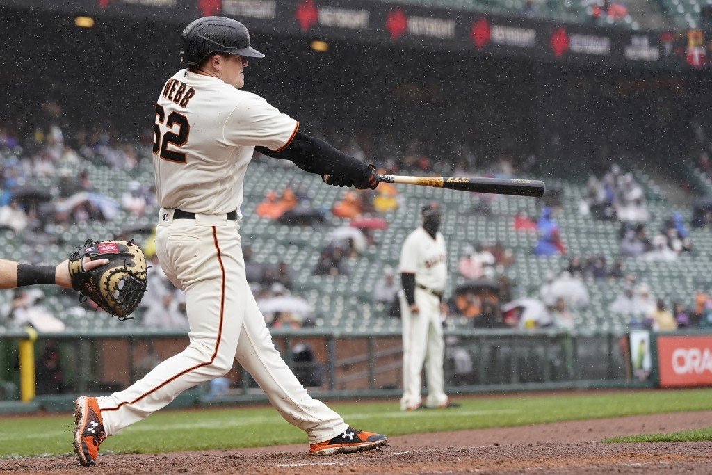 San Francisco Giants' Logan Webb hits a two-run triple against the Miami Marlins during the second inning of a baseball game in San Francisco, Sunday,...