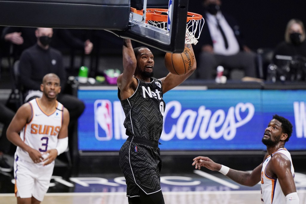 Phoenix Suns guard Chris Paul, left, and Suns center Deandre Ayton, right, watch as Brooklyn Nets forward Kevin Durant (7) dunks unopposed the third q...