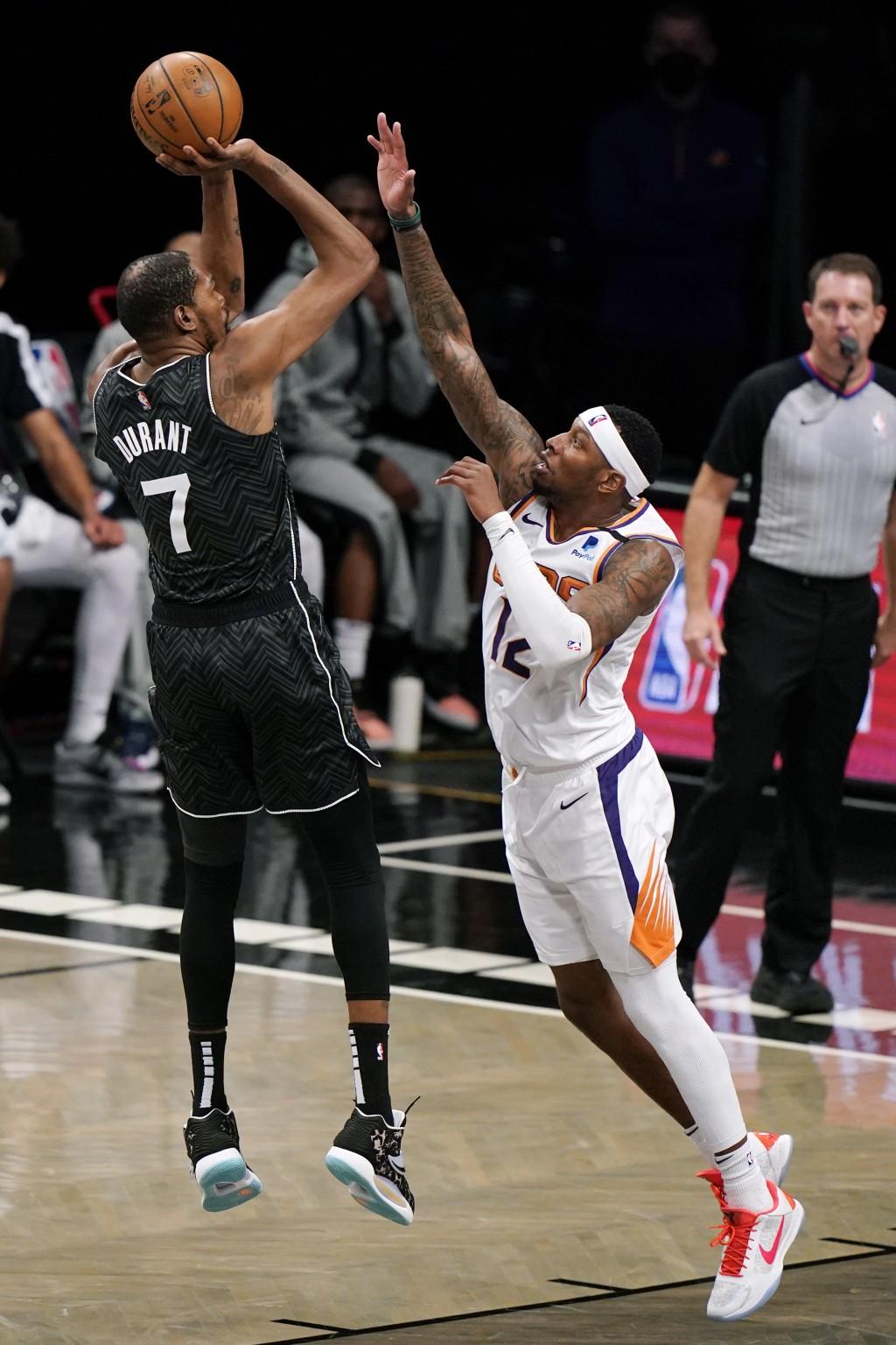 Phoenix Suns forward Torrey Craig (12) defends Brooklyn Nets forward Kevin Durant (7) as Durant shoots during the second quarter of an NBA basketball ...