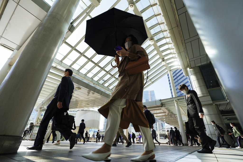Commuters wearing face masks walk in a passageway during a rush hour at Shinagawa Station Monday, April 26, 2021, in Tokyo. Japan declared a third sta...