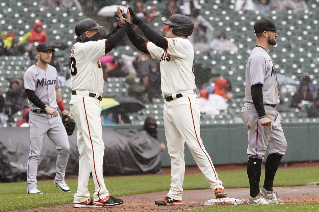 San Francisco Giants' Logan Webb, center, is congratulated by third base coach Ron Wotus after hitting a two-run triple against the Miami Marlins duri...