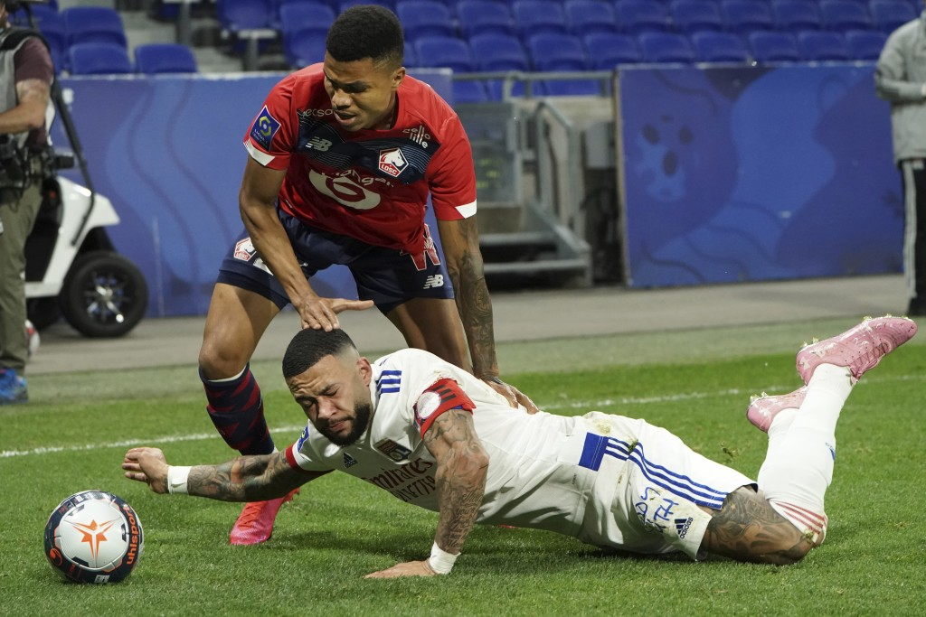 Lyon's Memphis Depay, down, challenges for the ball with Lille's Reinildo Isnard Mandava, up, during their French League One soccer match in Decines, ...