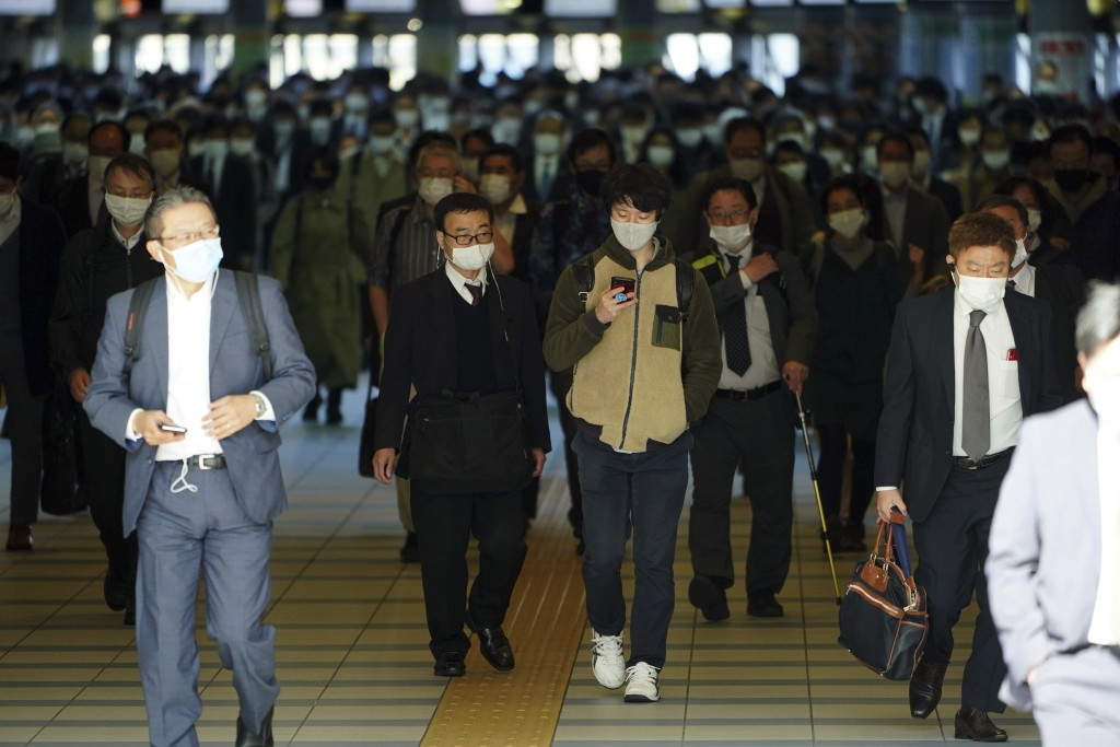 A station passageway is crowded with commuters wearing face masks during a rush hour at Shinagawa Station Monday, April 26, 2021, in Tokyo. Japan decl...