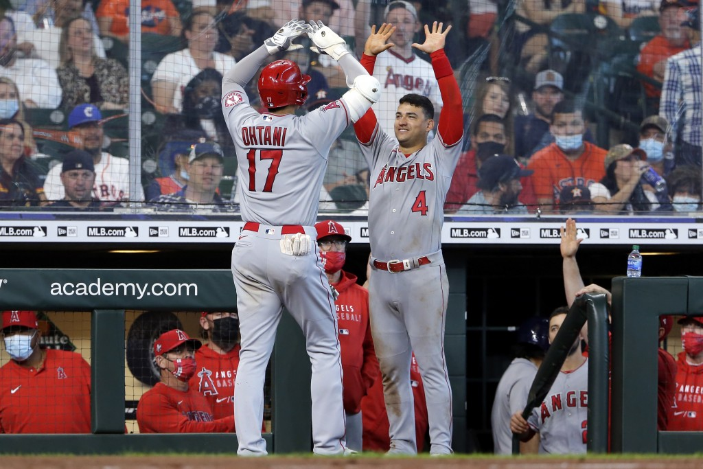 Los Angeles Angels designated hitter Shohei Ohtani (17) and Jose Iglesias (4) high five at the dugout after Ohtani's home run during the eighth inning...