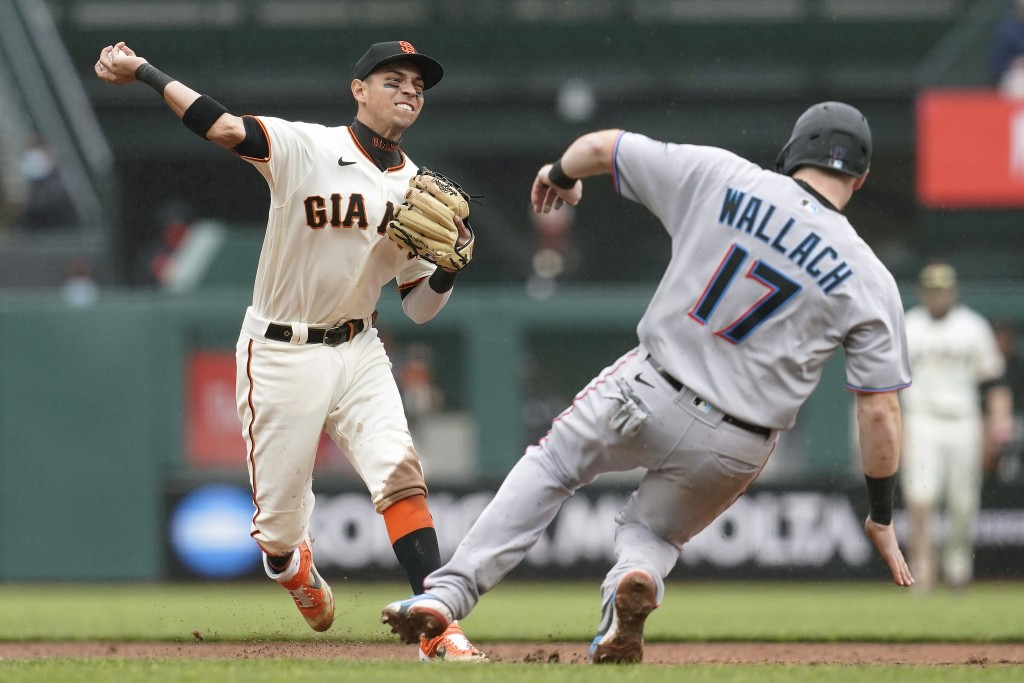 San Francisco Giants shortstop Mauricio Dubon, left, throws to first base after forcing out Miami Marlins' Chad Wallach (17) on a double play hit into...