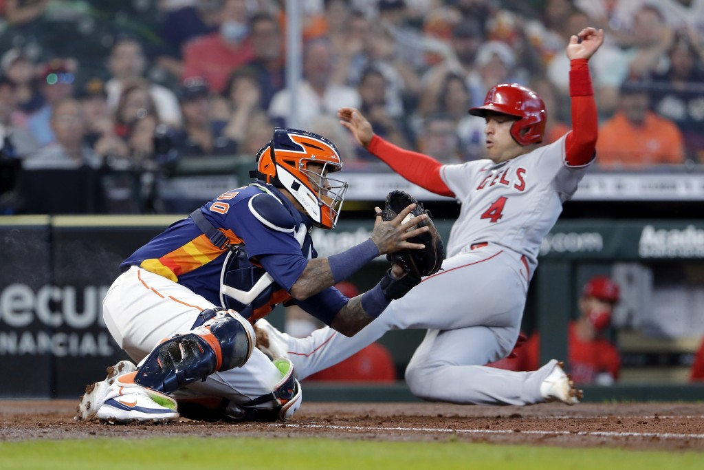 Houston Astros catcher Martin Maldonado, left, tries to make the tag against Los Angeles Angels' Jose Iglesias (4) as he safely slides into home plate...