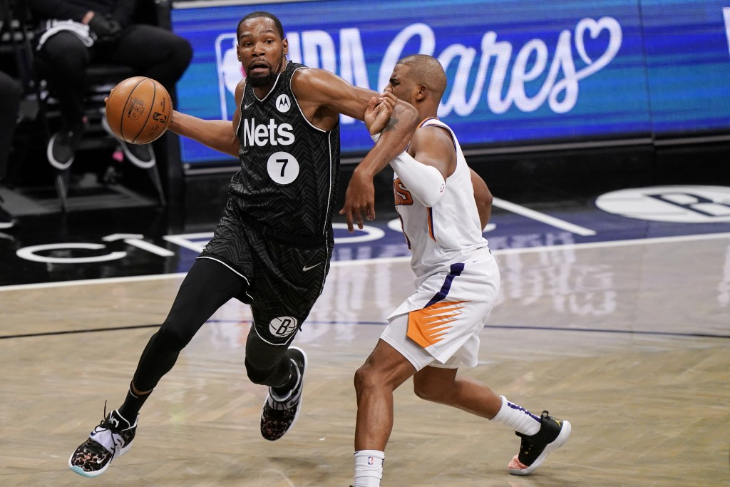 Brooklyn Nets forward Kevin Durant (7) becomes entangled with Phoenix Suns guard Chris Paul during the third quarter of an NBA basketball game, Sunday...