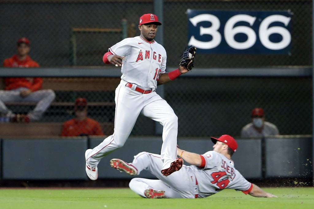 Los Angeles Angels left fielder Justin Upton (10) jumps to avoid right fielder Scott Schebler (44) as they both go to make the out on the fly by Houst...