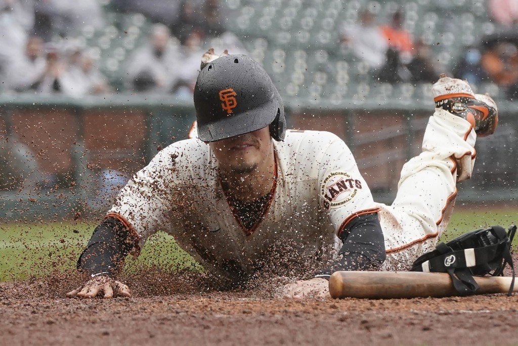 San Francisco Giants' Wilmer Flores slides home to score against the Miami Marlins during the second inning of a baseball game in San Francisco, Sunda...