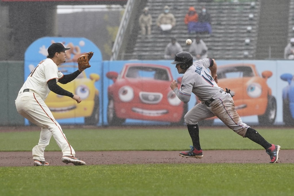 Miami Marlins' Adam Duvall, right, runs before being tagged out by San Francisco Giants' Wilmer Flores, left, during the second inning of a baseball g...