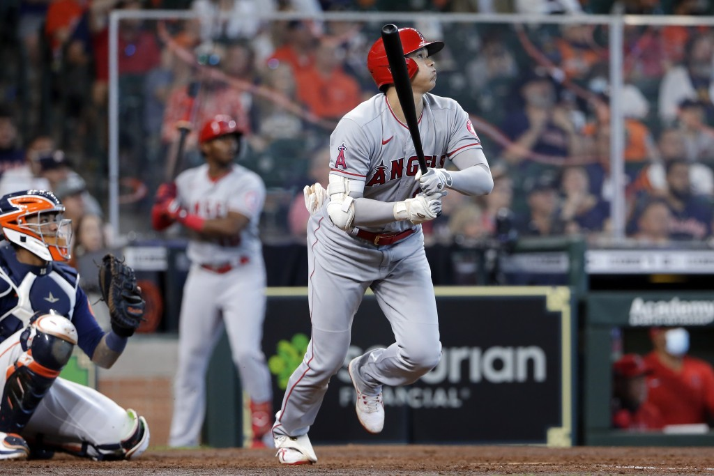 Los Angeles Angels designated hitter Shohei Ohtani, right, watches his home run hit in front of Houston Astros catcher Martin Maldonado, left, during ...
