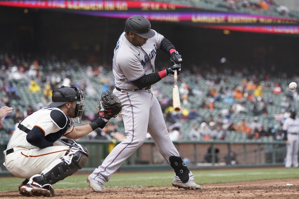 Miami Marlins' Jesus Aguilar, right, hits a two-run home run in front of San Francisco Giants catcher Curt Casali during the eighth inning of a baseba...