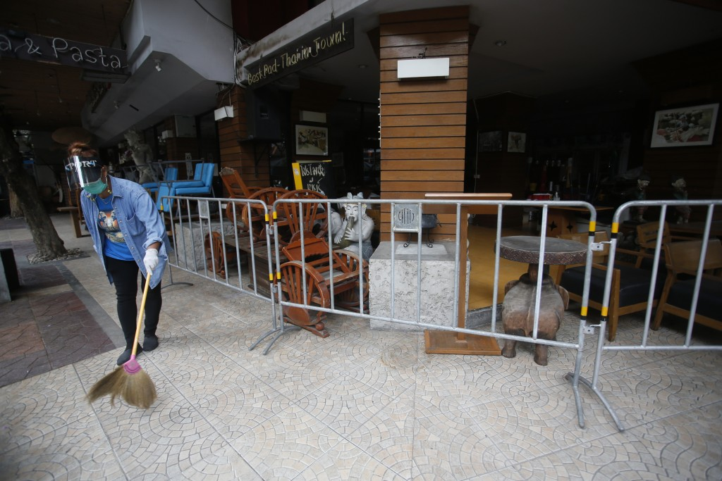A worker wearing a face mask to help curb the spread of the coronavirus sweeps with a broom around a restaurant in Khao San road, a popular hangout fo...