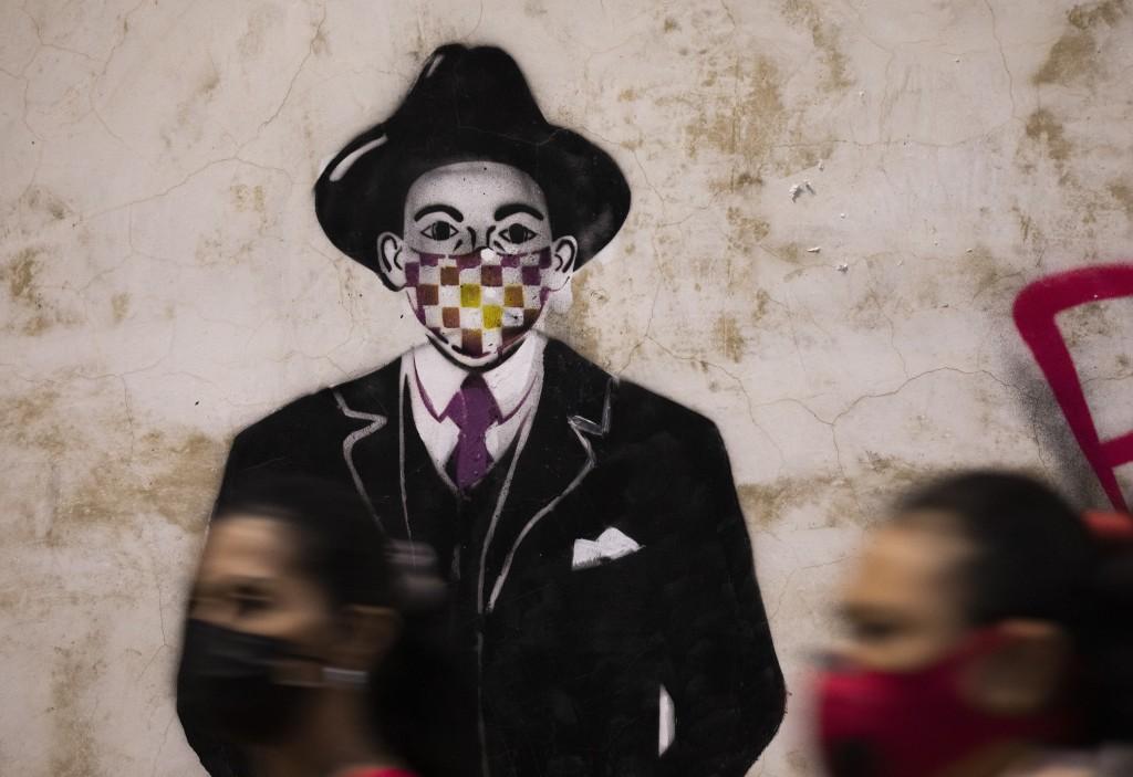 An image of Venezuelan popular saint, Dr. Jose Gregorio Hernandez wearing a mask is seen on a wall in Caracas, Venezuela, Monday, April 26, 2021. Know...