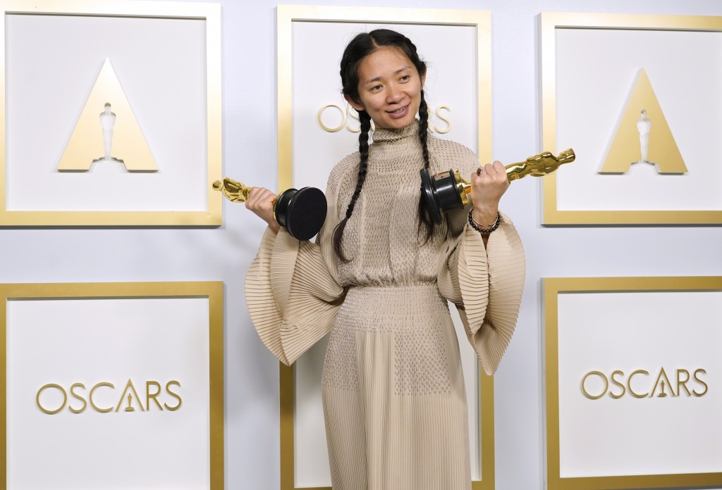 """Chloe Zhao, winner of the awards for best picture and director for """"Nomadland,"""" poses in the press room at the Oscars on Sunday, April 25, 2021, at Un..."""