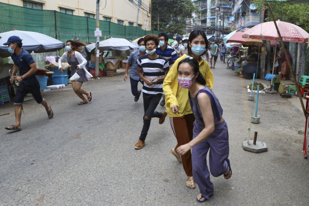 Anti-coup protesters run after seeing police and soldiers arrive to disperse their demonstration in Yangon, Myanmar, Tuesday, April 27, 2021. Demonstr...