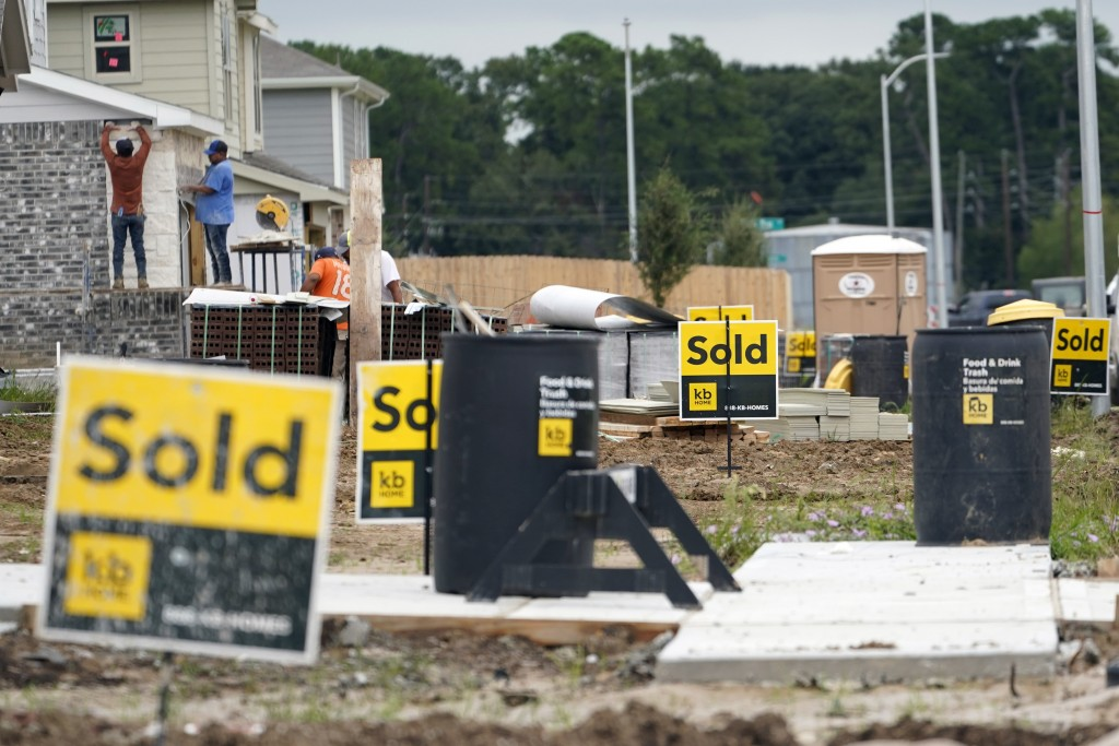 FILE - In this Sept. 24, 2020, file photo, construction workers build already sold new KB Homes in Houston. The first numbers from the 2020 census sho...
