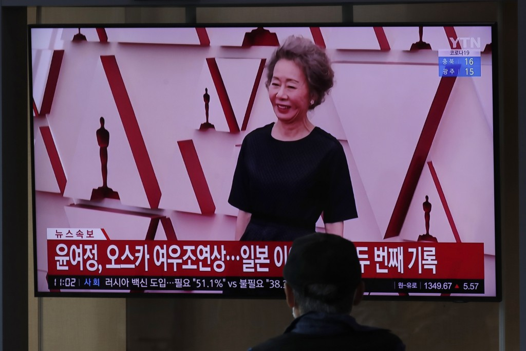A visitor watches a TV screen showing a news program with file footage reporting South Korean actress Yuh-Jung Youn received the Oscar for best suppor...