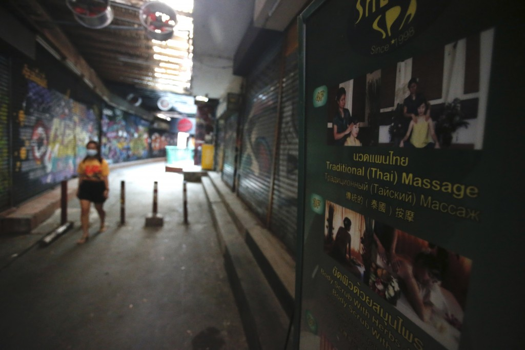 A passerby wearing a face mask to help curb the spread of the coronavirus moves past a closed massage shop in Khao San road, a popular hangout for Tha...