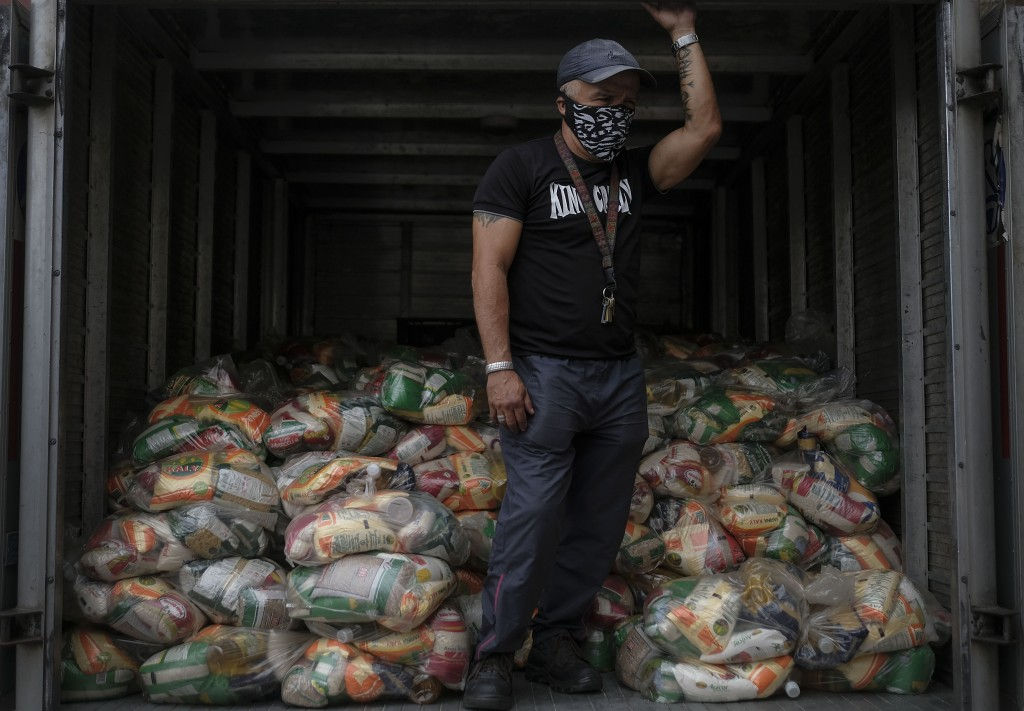 FILE - In this April 10, 2021 file photo, a man waits to unload bags of basic food staples, such as pasta, sugar, flour, and kitchen oil, provided res...