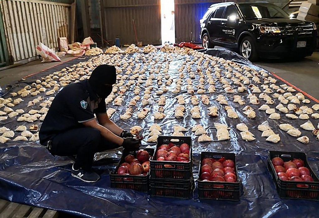 FILE - In this Friday, April 23, 2021 file photo, released by Saudi Press Agency, a Saudi custom officer opens imported pomegranates, as customs foile...