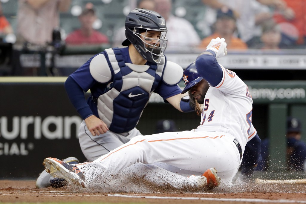 Seattle Mariners catcher Luis Torrens, left, makes an empty glove tag as Houston Astros designated hitter Yordan Alvarez, right, is safe on the slide ...
