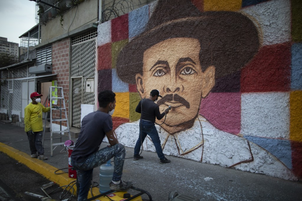 Venezuelan artist Miguel Garcia puts on the finishing touches on his mural of Venezuelan popular saint, Dr. Jose Gregorio Hernandez, in Caracas, Venez...