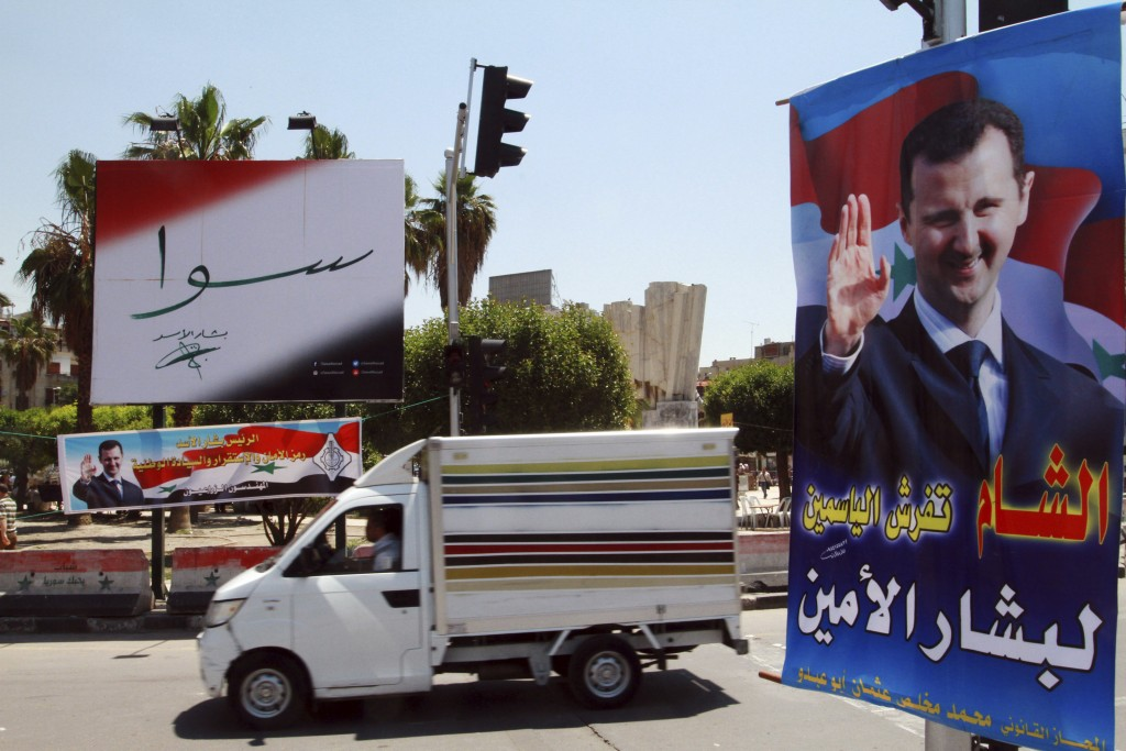 FILE - In this May 12, 2014 file photo, campaign posters for the upcoming presidential election adorn a street in Damascus, Syria. On Monday April 26,...