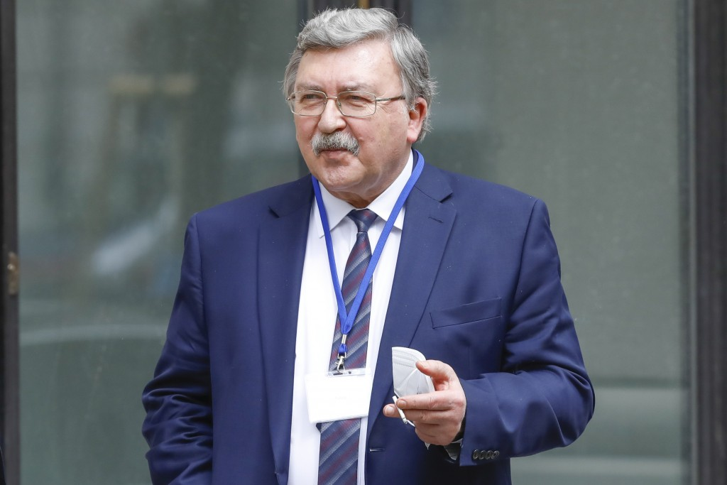 FILE - In this April 20, 2021 file photo Russia's Governor to the International Atomic Energy Agency, IAEA, Mikhail Ulyanov smokes a cigarette in fron...