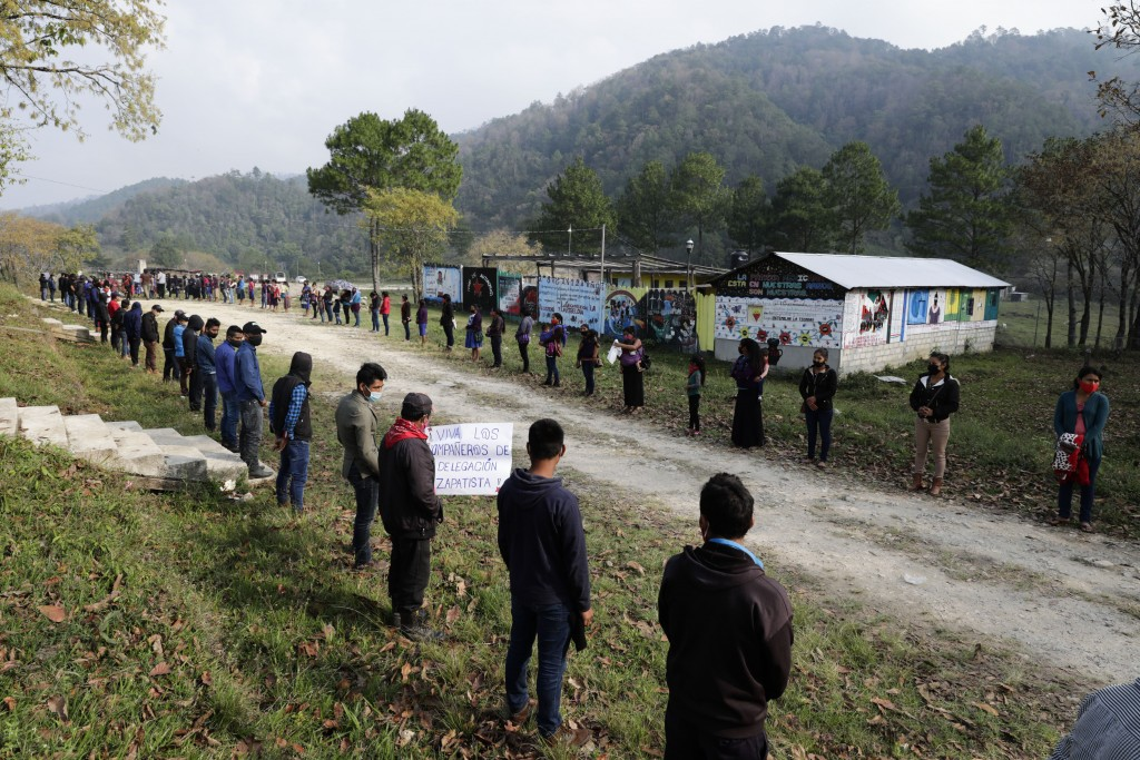 Members of the Zapatista Army of National Liberation, EZLN, line up on the side of the road to bid farewell to a delegation that will leave for Europe...