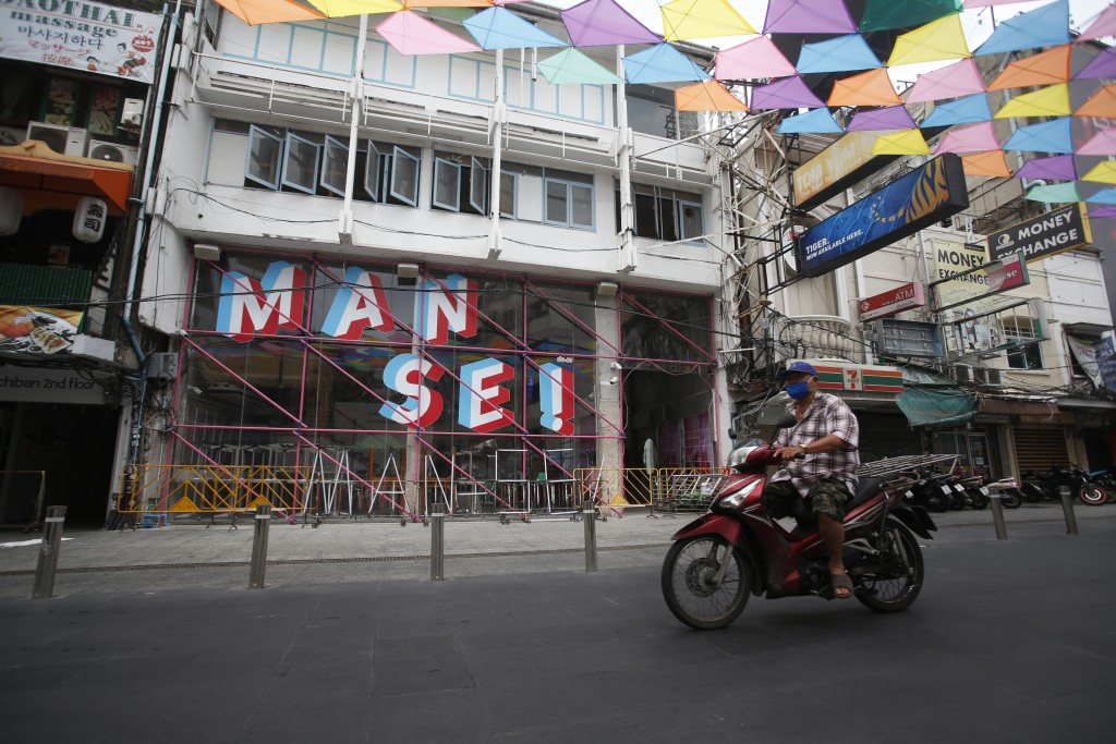A motorcyclist wearing a face mask to help curb the spread of the coronavirus moves past Khao San road, a popular hangout for Thais and tourists in Ba...