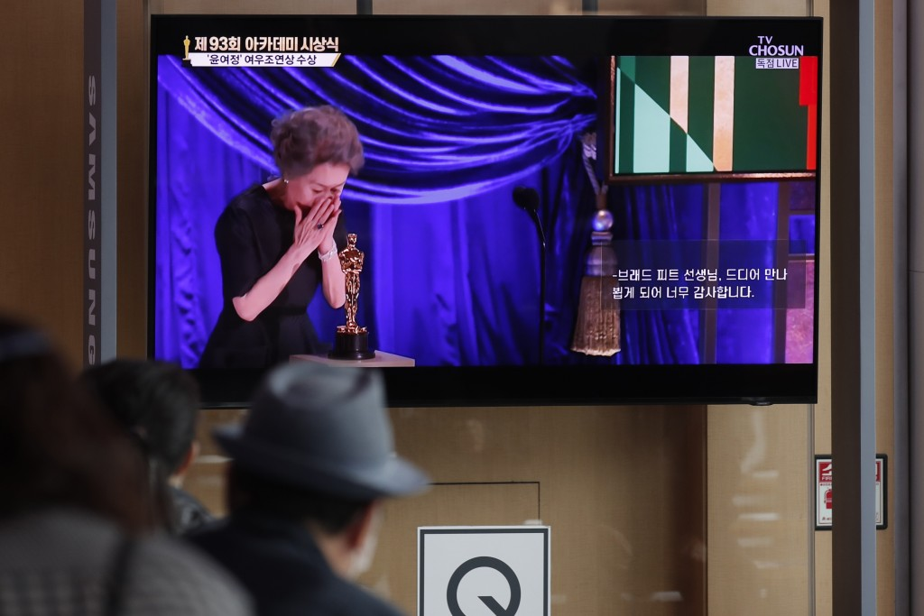 """People watch live broadcast on TV showing South Korean actress Yuh-Jung Youn receiving the Oscar for best supporting actress for her performance in """"M..."""