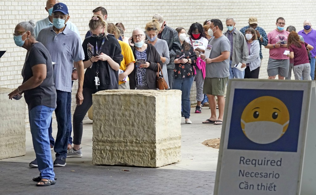 Wearing face masks to prevent the spread of COVID-19, voters line up to cast their ballot during early voting Tuesday, April 27, 2021, in Mansfield, T...