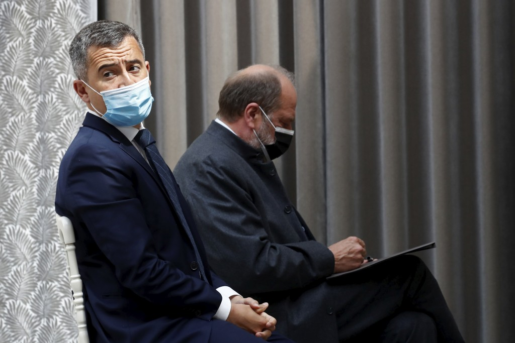 French Interior Minister Gerald Darmanin, left, and Justice Minister Eric Dupond-Moretti, wearing protective face masks, attend a news conference foll...