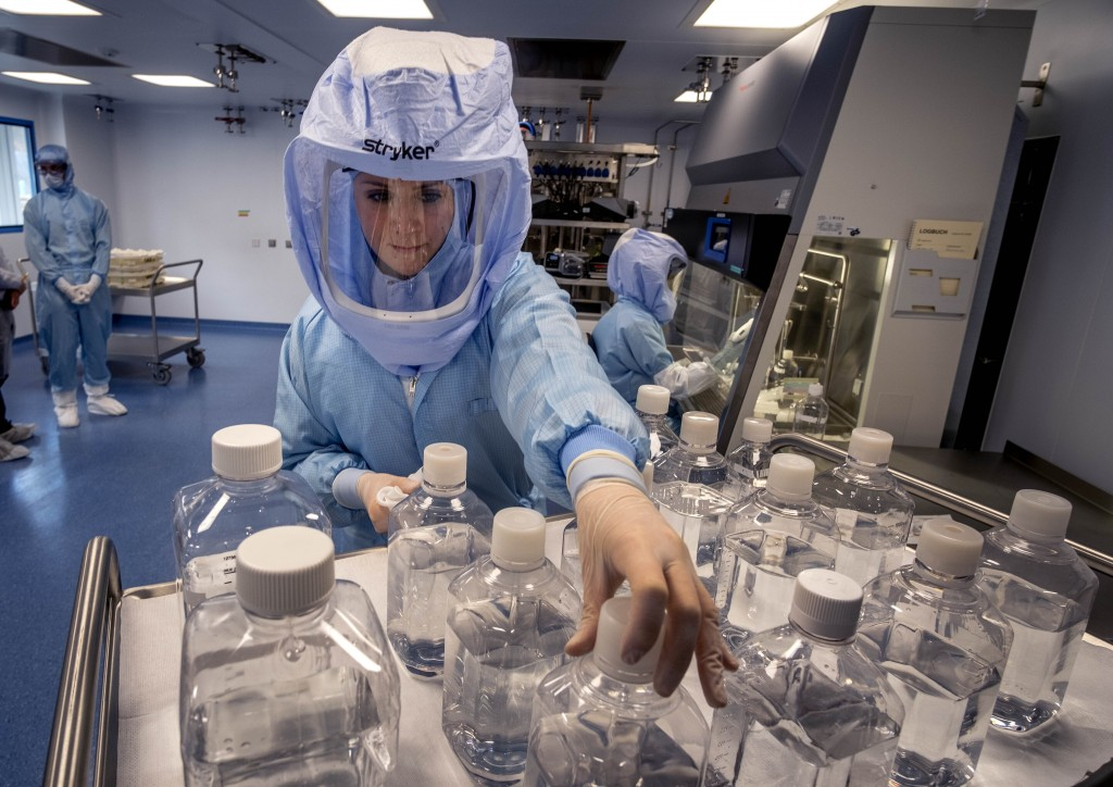 FILE - In this March 27, 2021 file photo a laboratory worker simulates the workflow in a cleanroom of the BioNTech Corona vaccine production in Marbur...