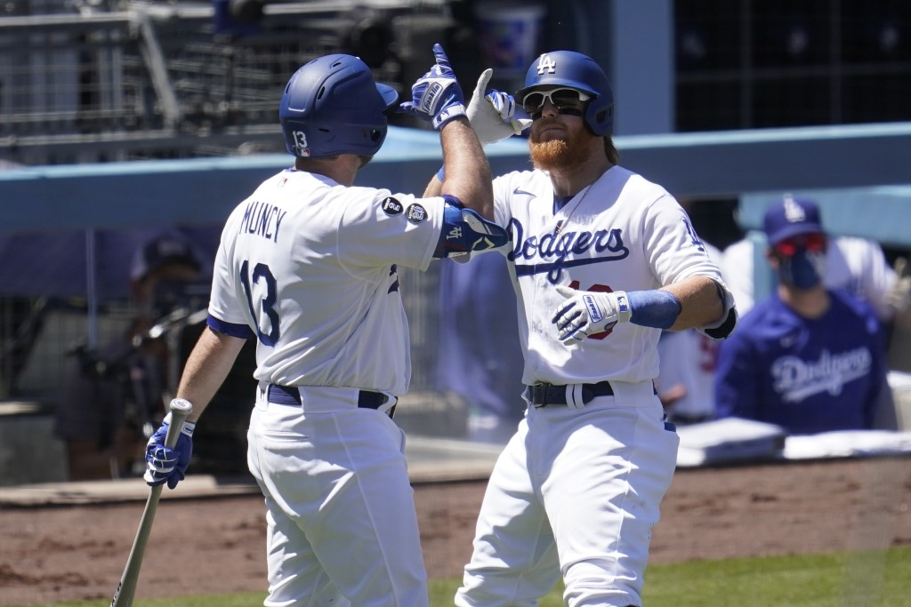 Los Angeles Dodgers' Justin Turner, right, celebrates his solo home run with Max Muncy during the third inning of a baseball game against the Cincinna...
