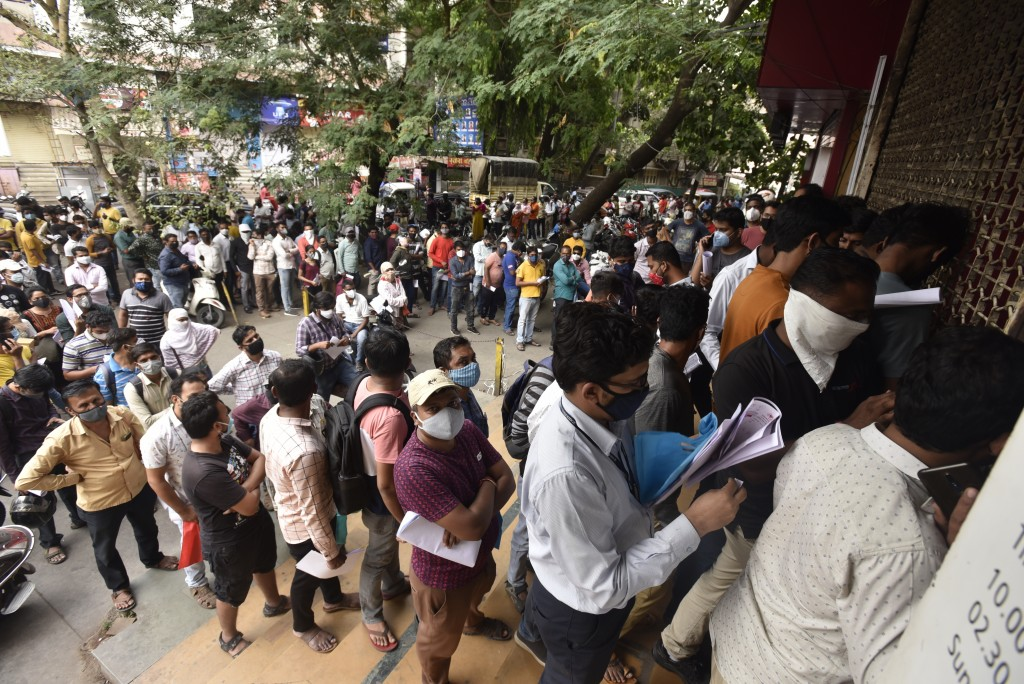 FILE- In this April 8, 2021 file photo, people wait in queues outside the office of the Chemists Association to demand necessary supply of the anti-vi...