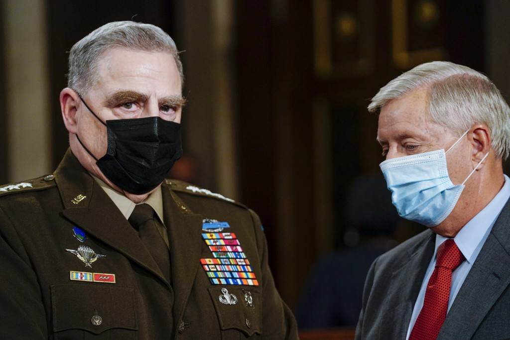 Joint Chiefs Chairman Gen. Mark Milley, left, and Sen. Lindsey Graham, R-S.C., talk as they arrive the chamber ahead of President Joe Biden speaking t...