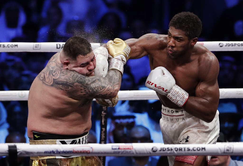 FILE - Defending champion Andy Ruiz Jr., left, takes a right cross to the face during his fight against Britain's Anthony Joshua in their World Heavyw...