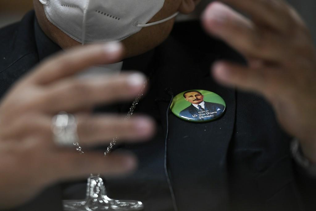 Monsignor Tulio Ramirez wears a pin of the late Dr. Jose Gregorio Hernandez during an interview about Hernandez's beatification in Caracas, Venezuela,...