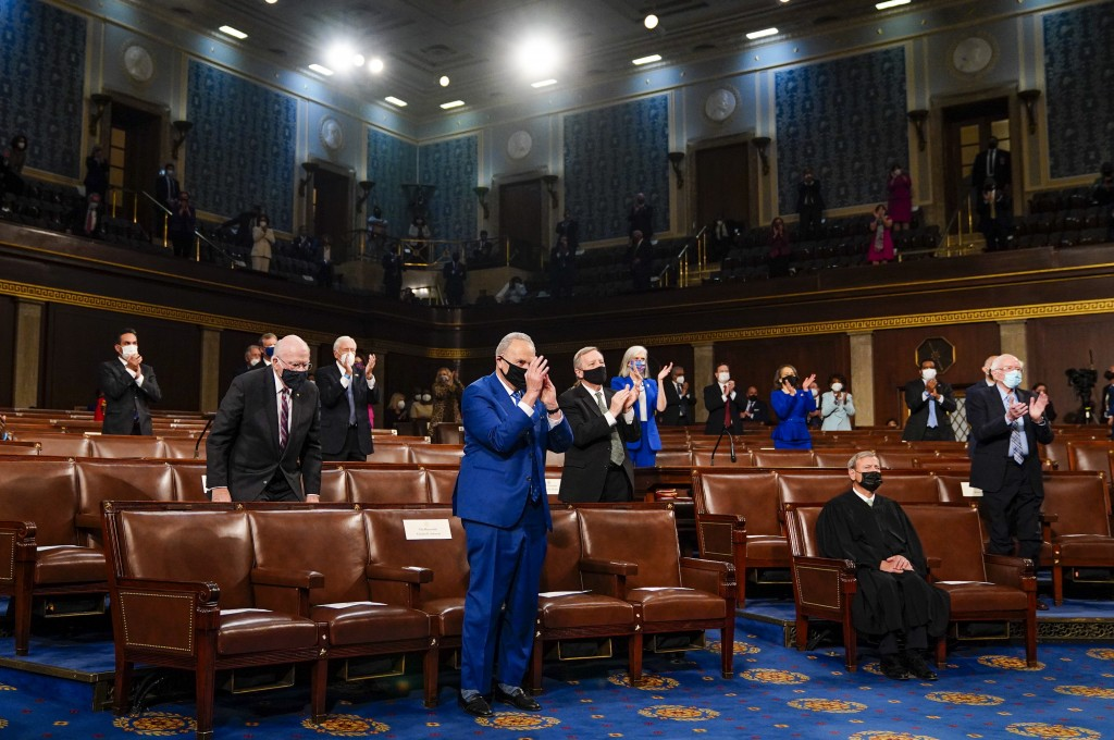 Senate Majority Leader Chuck Schumer of N.Y., stands and applauds as President Joe Biden addresses a joint session of Congress, Wednesday, April 28, 2...