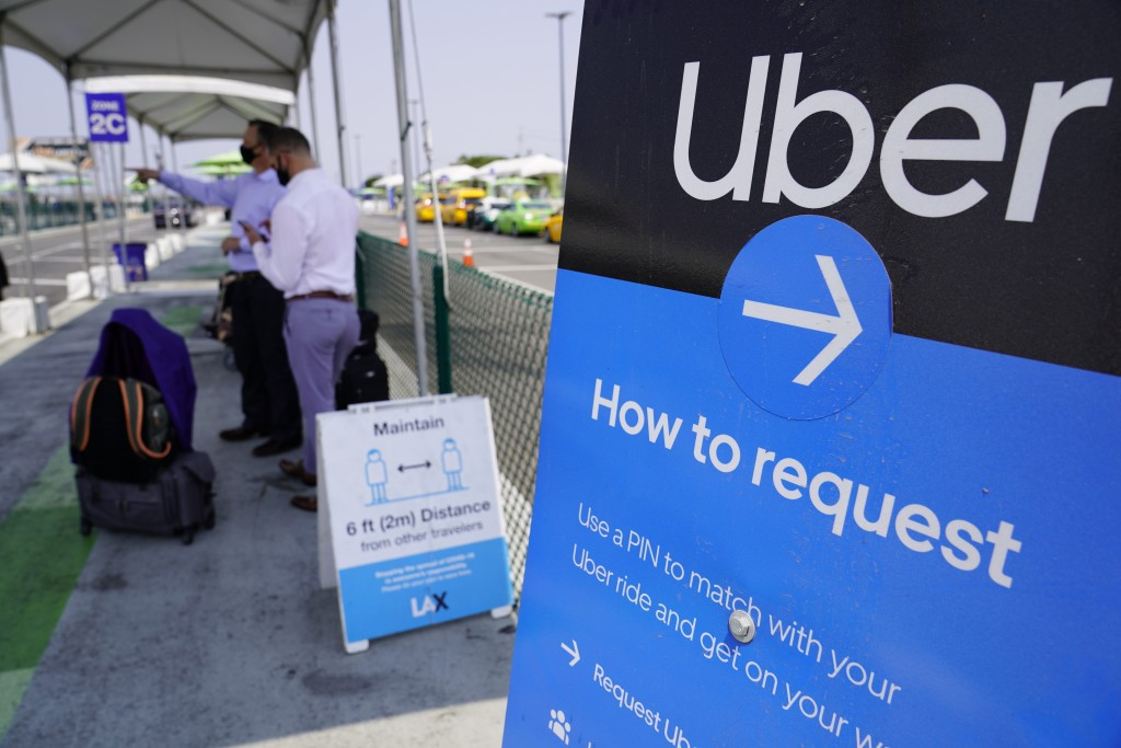 In this Aug. 20, 2020, file photo travellers request an Uber ride at Los Angeles International Airport, USA.