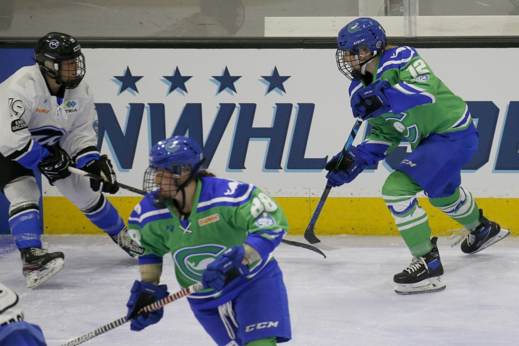 FILE - Connecticut Whale defender Maggie LaGue (12) moves the puck up the ice as Minnesota Whitecaps forward Haley Mack (19) defends during the first ...