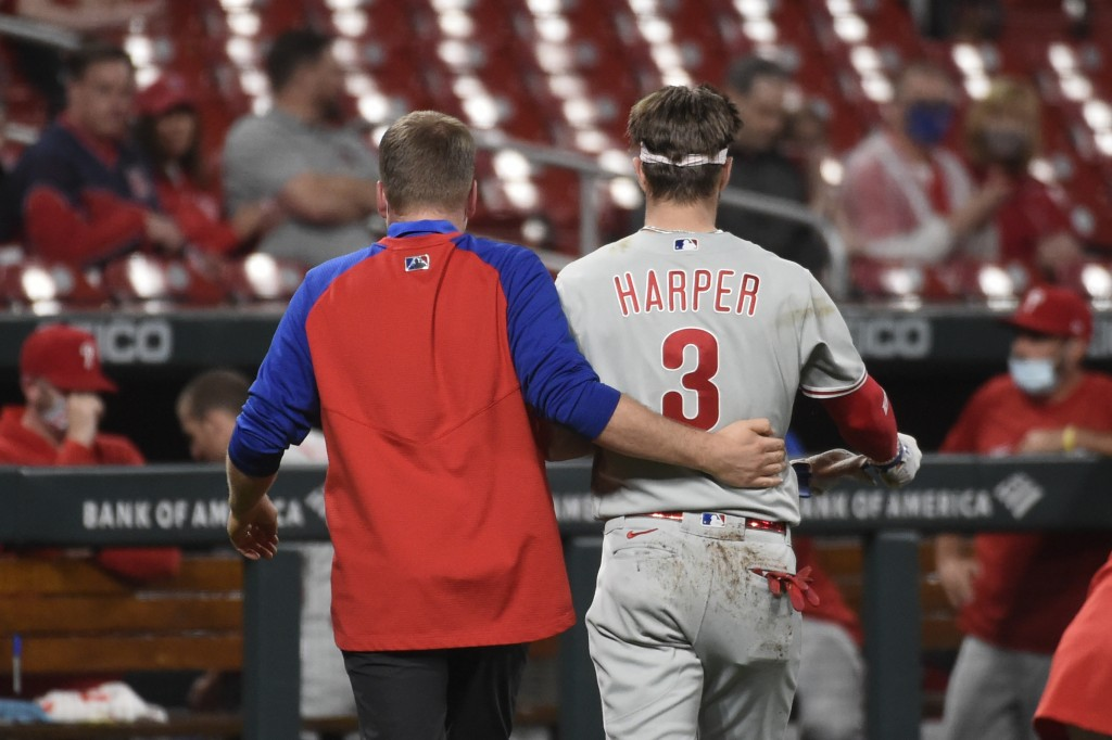 Philadelphia Phillies right fielder Bryce Harper, right, is helped off the field after getting hit by a pitch during the sixth inning of the team's ba...