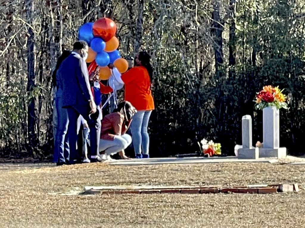 FILE - In this Feb. 23, 2021, file photo, Wanda Cooper-Jones kneels before the grave of her son, Ahmaud Arbery, at the New Springfield Baptist Church ...