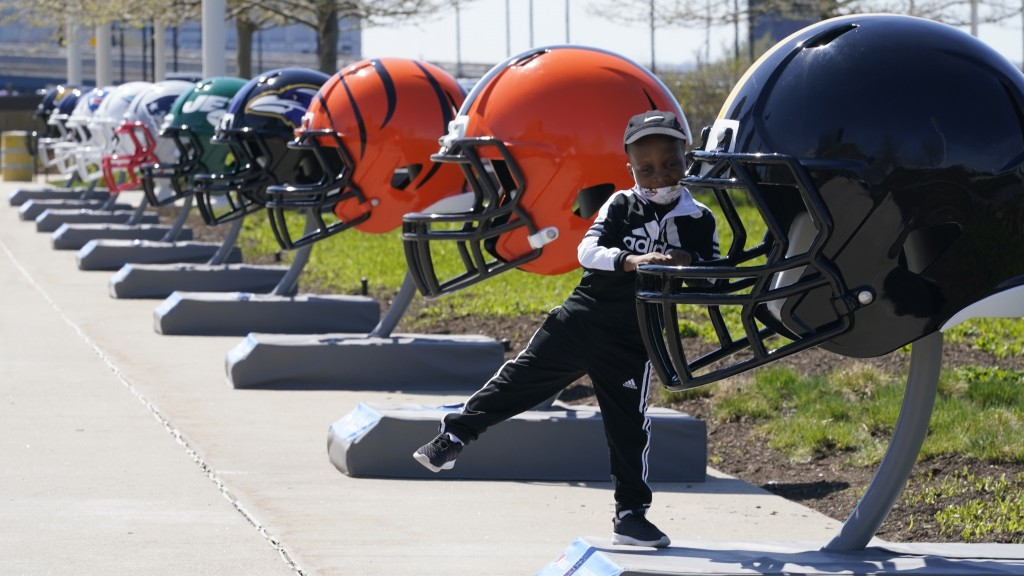 Joseph Toliver, 4, plays on one of the 32 NFL team helmets on display, Tuesday, April 13, 2021, in downtown Cleveland. Forced to cancel last year's NF...