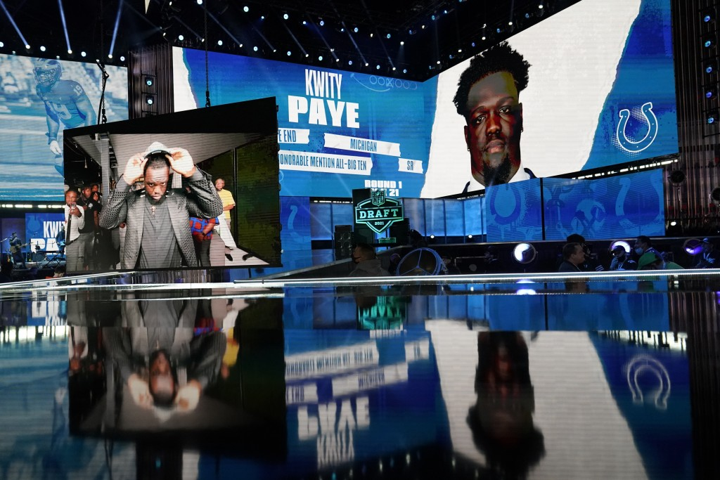 Images of Michigan defensive lineman Kwity Paye are displayed on stage after he was chosen by the Indianapolis Colts with the the 21st pick in the fir...