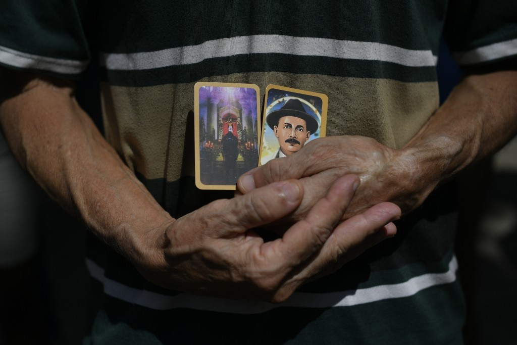 A man holds images of the late, Venezuelan Dr. Jose Gregorio Hernandez on the day of his Beatification ceremony outside the church that guards his rem...